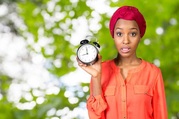 Женщина держит, с тревогой глядя на часы