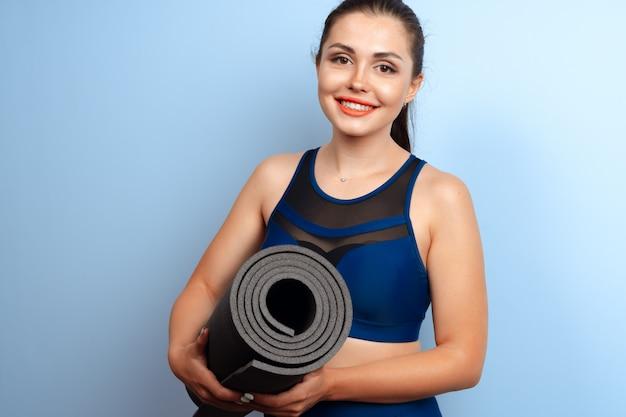 Молодая стройная женщина держит в руках коврик для йоги