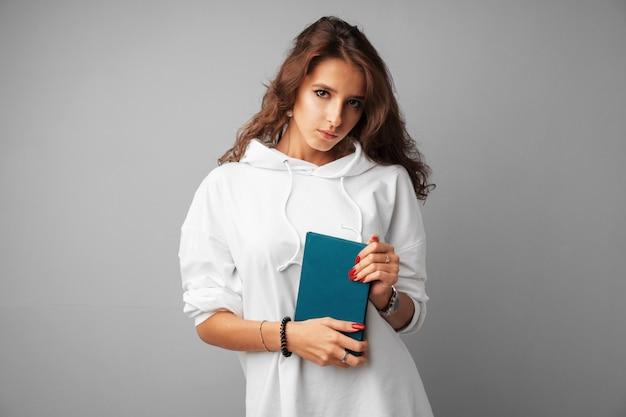 灰色の背景の上に彼女の手で本を持って白いパーカーの学生少女ティーンエイジャー
