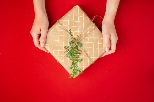 Готовясь к новогодним праздникам, женщина с подарком в руках