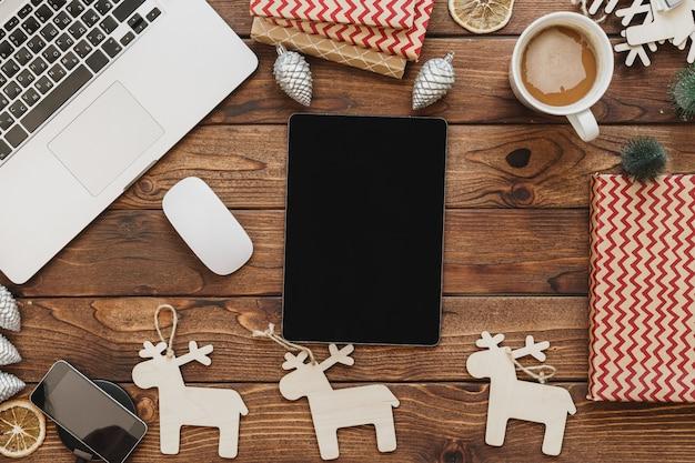 オフィス用品やクリスマスの装飾とコンピューターで木製デスクトップのトップビュー