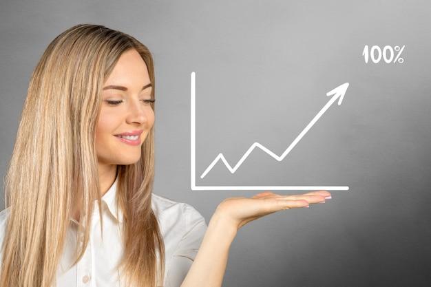 背景に描かれたビジネスグラフを持つ若い女性