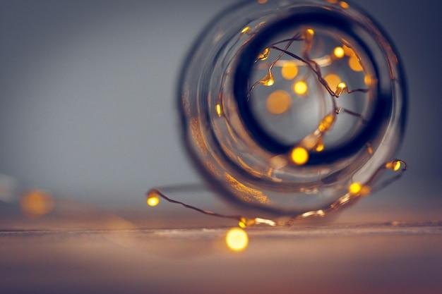 Огни гирлянды в стеклянной бутылке на темном фоне