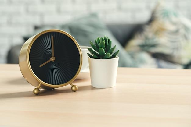 木製のテーブルに昔ながらの目覚まし時計と観葉植物