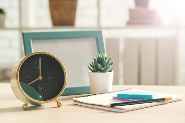 木製のテーブルの目覚まし時計とオフィス文房具オブジェクト