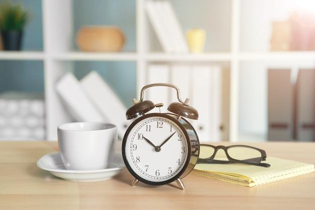 Детали интерьера офиса с будильником и канцелярскими товарами