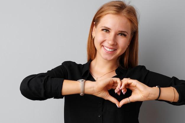 Молодая красивая женщина, касаясь ее сердце своими руками на сером фоне