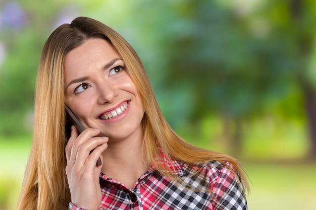 若い幸せな白人女性は携帯電話で呼び出しています