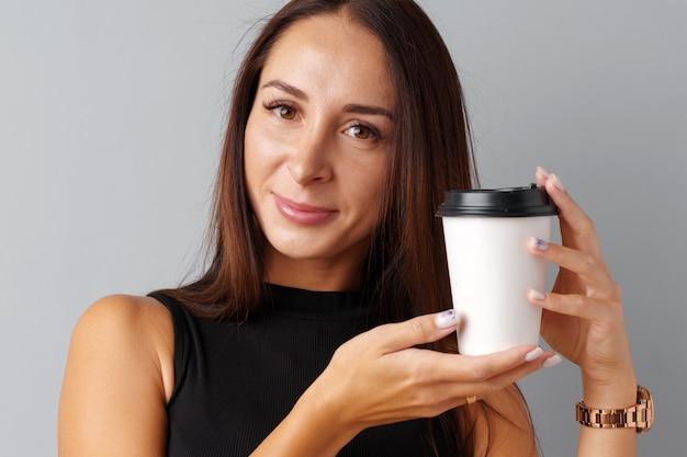 Славная брюнетка молодая женщина держит чашку кофе на сером фоне