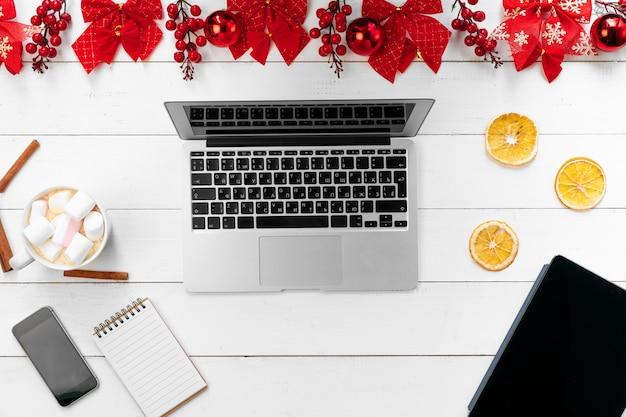 Ноутбук на белом деревянном столе в окружении красных рождественских украшений