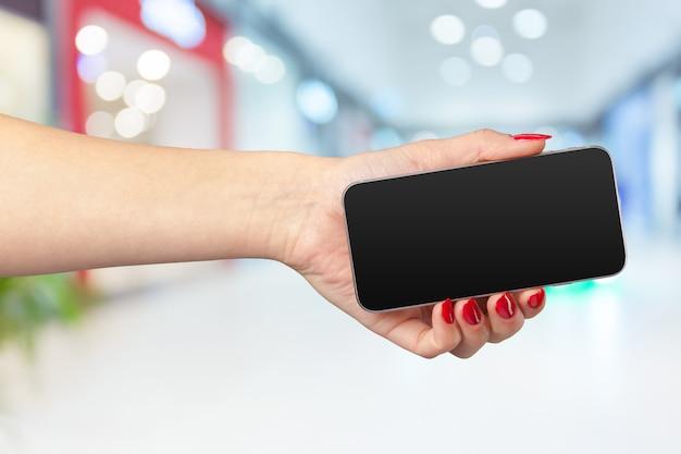 Макет смартфон с пустым экраном в руках женщины