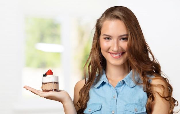 ジレンマダイエット中の女性アップルとカップケーキの未定の女性
