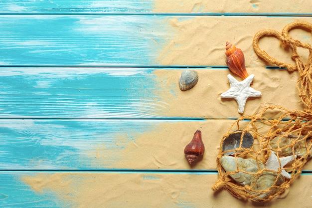 青い木製の背景に海の砂の上の多くの異なる海の貝と海ロープ