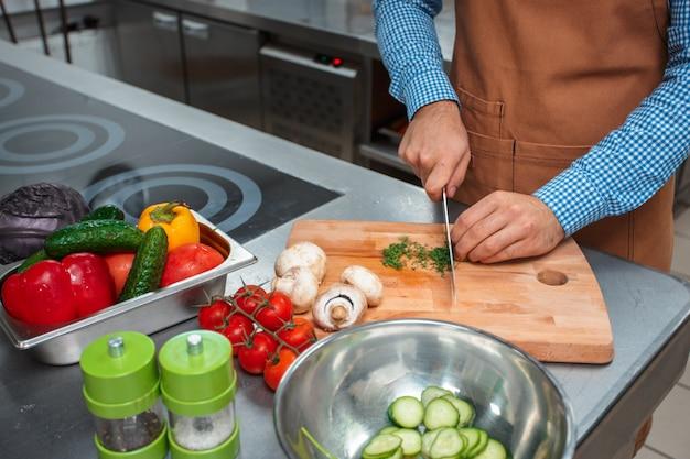 レストランのキッチンで料理をして茶色のエプロンのシェフ