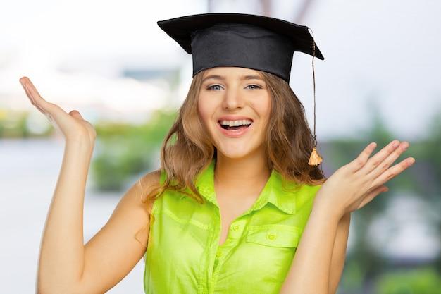 Счастливый студент в выпускной колпачок