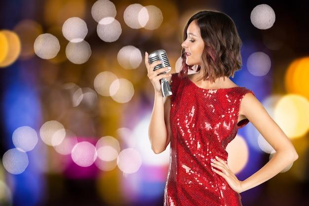 Женщина певица в красном блестящем платье