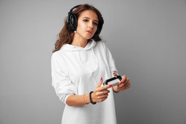 Молодая милая женщина играя с джойстиком консоли над серым цветом