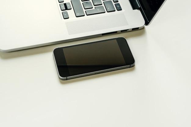 開いているノートパソコンの近くの黒いスマートフォンのクローズアップ
