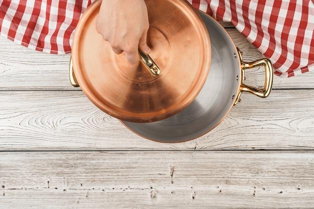 木製の上面に料理人の手で光沢のある銅鍋