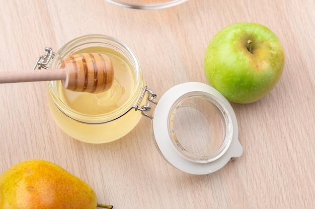 Еврейский праздник рош ха-шана с медом и яблоками на деревянный стол.