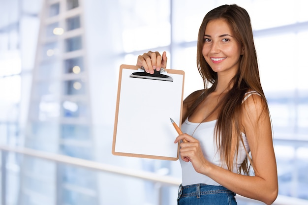 幸せな笑顔若い美しいビジネス女性とクリップボード