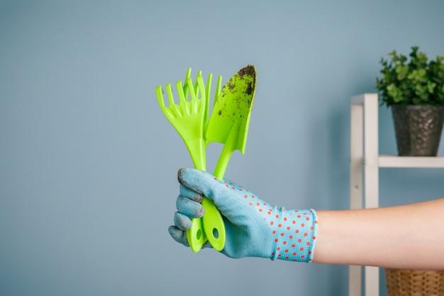 Рука садовые инструменты на синем