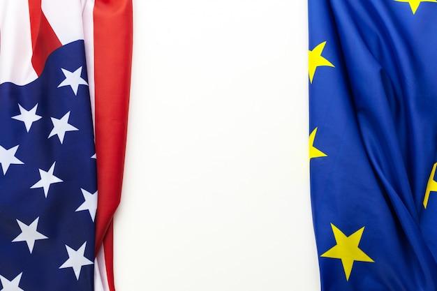 テーブルの上に一緒に横になっている米国および欧州連合の旗のクローズアップ