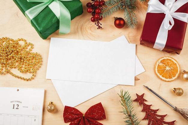 Поздравительное письмо, конверт и перо в окружении елочных украшений