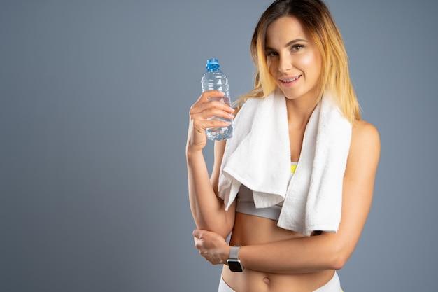 水のボトルを保持している灰色の背景上のスポーティな女性
