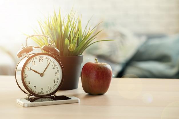 ビンテージの目覚まし時計と木製の机の上のリンゴ