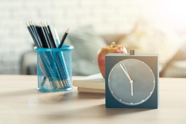 目覚まし時計と木製の机の上のリンゴ