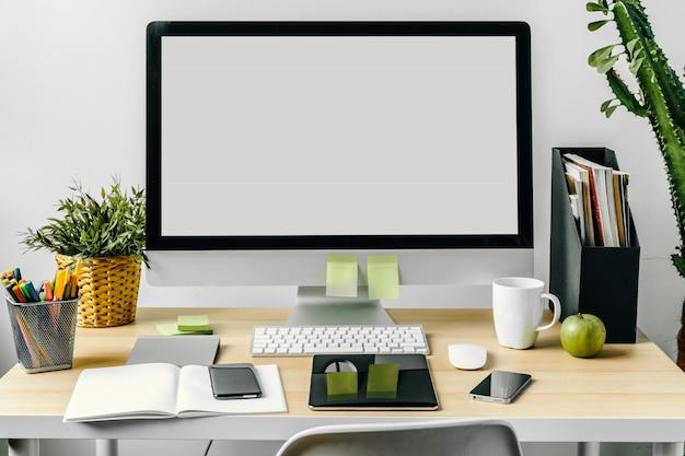 Монитор компьютера с макетом белый экран на офисном столе с расходными материалами