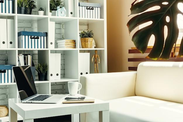 ソファ、家の内部の近くのテーブルでノートパソコンを開きます。フリーランサー職場のコンセプト