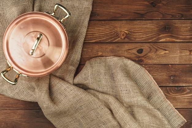 暗い木製のテーブルの上の銅鍋