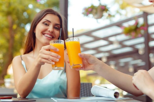 Две красивые молодые девушки сидят за столом в кафе