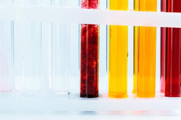 Различная лабораторная посуда с цветными жидкостями
