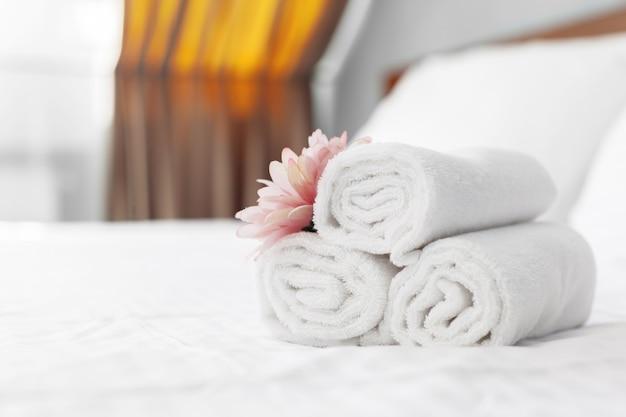 Полотенца и цветок на кровати в гостиничном номере