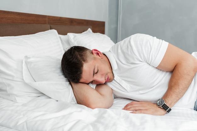 仕事で厳しい日の後ベッドでリラックスした若いハンサムな男