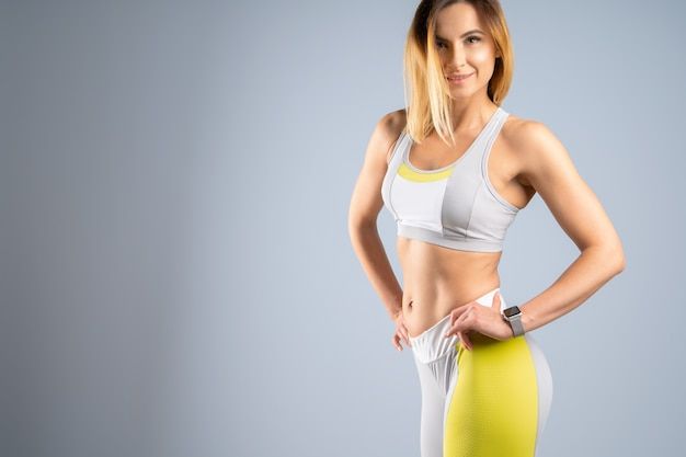 Молодая спортивная пригонка кавказской женской модели на сером фоне