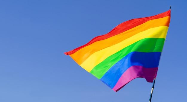 澄んだ青い空に風になびかせてゲイ虹色の旗