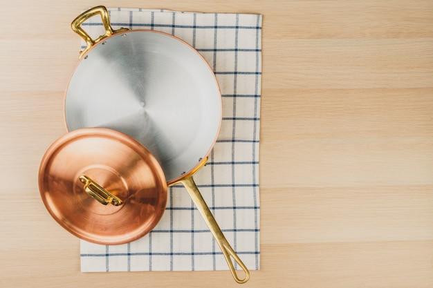 木製の背景、上面に銅フライパン