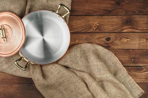 暗い木製のテーブル、トップビューで銅鍋