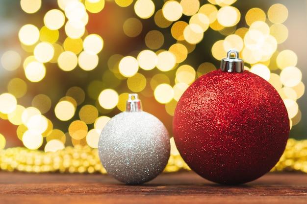 ぼやけた光沢のあるボケ背景に木製のテーブルでクリスマスボール