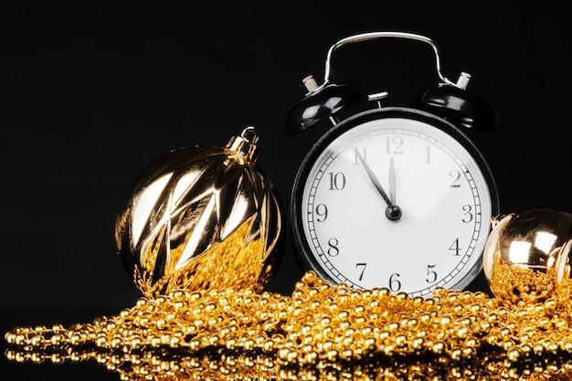 クリスマスつまらないと暗い黒の背景に装飾が施された黒のビンテージ目覚まし時計。クリスマスイブのコンセプト
