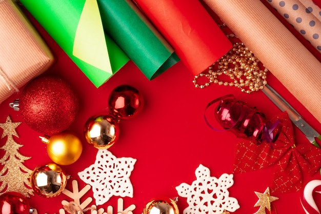 包装紙と赤の背景に飾るクリスマスのアイテムのショットを閉じる