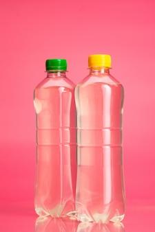 明るいピンクの背景に色の飲み物やレモネードのボトルをクローズアップ
