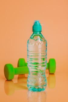 パステルベージュの背景にプラスチック製の水ボトル