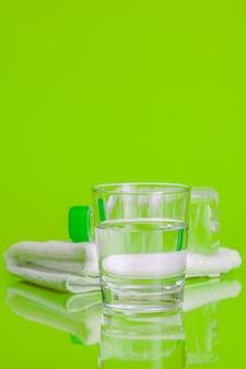 緑の背景にミネラルウォーターのガラスカップ