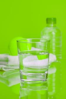 Стеклянная чашка минеральной воды на зеленом фоне