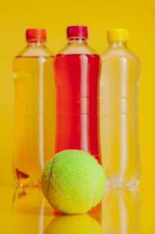 明るい黄色の背景に飲み物の完全なプラスチックボトル